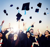 Cheerful Students Throwing Graduation Caps In The Air — Stock Photo