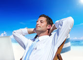 Businessman relaxing on beach — Stock Photo