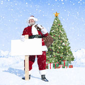Santa claus holding sack and placard — Stock Photo