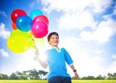 Boy outdoors with helium balloons — Stock Photo