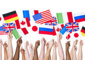 Flagshands holding different flags — Stock Photo