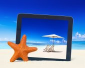 Tablet computer with idyllic beach — Stock Photo