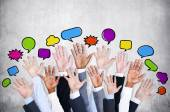 Business people's arms with speech bubbles — Stock Photo