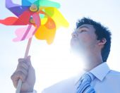 Businessman blowing pinwheel — Stock Photo