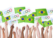 Hands holding flags of Brazil Olympics 2016 — Stock Photo