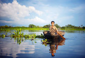 Cambodian boy travelling by boat — Stock Photo