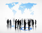 Business people beneath the world map — Stock Photo