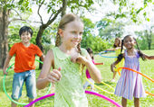 Children Playing with hula hoops in the park — Stock Photo
