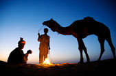Two men by bon fire with camel — Stock Photo