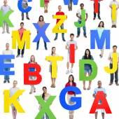 Multi-ethnic people holding alphabet — Stock Photo