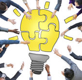Business People Forming Light Bulb Puzzle — Stock Photo