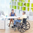 Businesswoman and man in wheelchair in office — Stock Photo #52465283