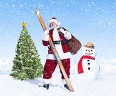 Santa claus holding sack and skis — Stock Photo