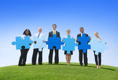 Business people holding puzzle on hill — Stock Photo