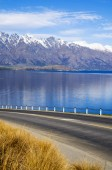 Road with lake and mountain range — Stok fotoğraf