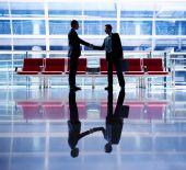 Businessmen talking in airport — Stockfoto