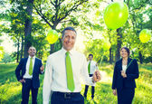 Business people holding green balloons — Stock Photo