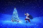 Santa claus holding lantern and sack — Stock Photo