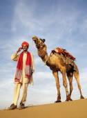 Guide and camel (Jonnie) in desert — Stock fotografie