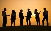 Business people on the hill at sunset — Stock Photo