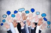 Business arms raised with speech bubbles — Stock Photo