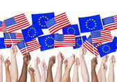Hands holding EU and Americain Flags — Stock Photo