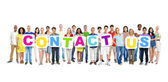 People holding cardboards forming contact us — Stock Photo