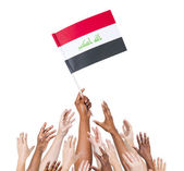 Human hands holding Iraq Flag — Stock Photo