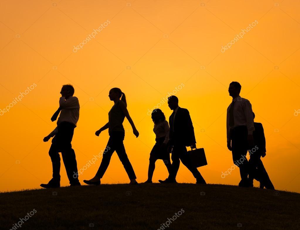 Siluetas De Personas Caminando Al Atardecer