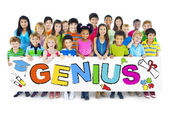 Children holding word Genius — Stock Photo