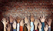 Hands Raised on Brick Wall — Stock Photo