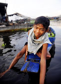 Boy traveling by boat in floating village — Stock Photo
