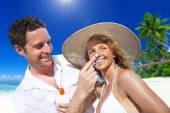 Couple applying sun protection on beach — Stock Photo