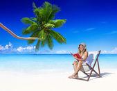 Woman reading at beach — Stock Photo