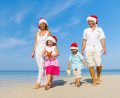 Family on beach in Christmas hats — Stock Photo