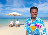 Man in front of couple relaxing on the beach — Stock Photo