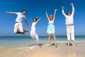 Two couples celebrating on the beach — Stock Photo