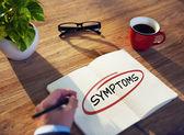 Businessman Writing Word 'Symptoms' — Stock fotografie