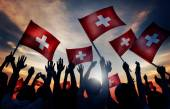 Silhouettes of People Holding Flags of Switzerland — Stock Photo
