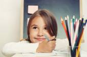 Portrait of cute lovely girl drawing in copybook on blackboard b — Stock Photo