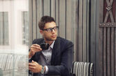 Young attractive businessman drinking espresso coffee in the cit — Stock Photo