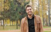 Portrait of attractive happy smiling stylish young man in autumn — Stock Photo