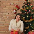 Beautiful exciting young woman with presents near Christmas tree — Stock Photo #57925297