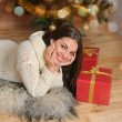 Beautiful smiling young woman with presents near Christmas tree  — Stock Photo #57925781