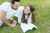 Couple of young students studing on the grass by the campus — Stock Photo