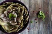 Artichoke like lotus flower on bowl on wooden rustic table — Stock Photo