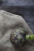 One artichoke on jute sack on wooden rustic table — Stock Photo