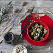 Roasted japanese turnips with leaves and seeds on red bowl on rustic background — Stock Photo #53244237
