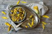 Summer flowers pasta with seeds and petals flowers and yellow spices on rustic background — Stock Photo