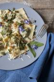 Italian handmade ravioli with borage herb, flowers, sage and crisp onion on plate — Stock Photo